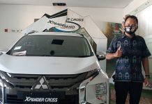 PENJUALAN : Sales Supervisor PT Berlian Cahaya Bima Lombok, Raka Indra Dwi Septa fose disamping salah satu produk Mitsubishi. (FAISAL HARIS/RADAR LOMBOK)